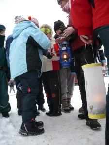 Nejmladší skauti a skautky z Police nad Metují si připalují Betlémské světýlko.